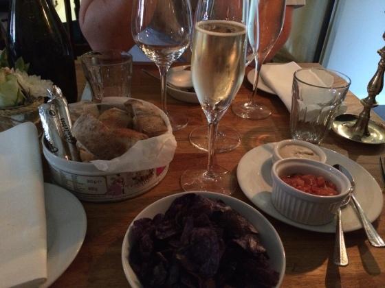 Velkomst bobler, oliven, svampecreme, tomatsalsa, friskbagtbrød og blå franske kartoffelchips.